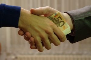 Illegal Bribe Whistleblower Reward: Handshake exchanging euro currency.